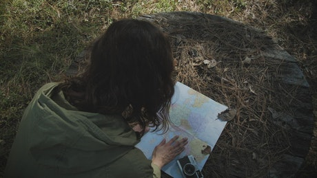 Woman reading a map in the forest