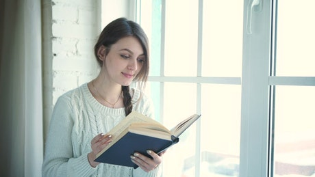 Woman reading book near bright window