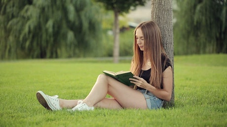 Woman reading in the park next to a tree