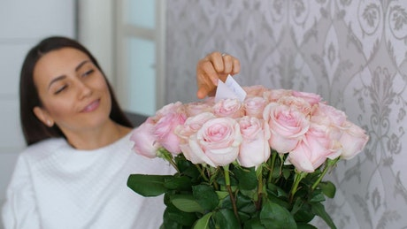 Woman reads the note on her bouquet