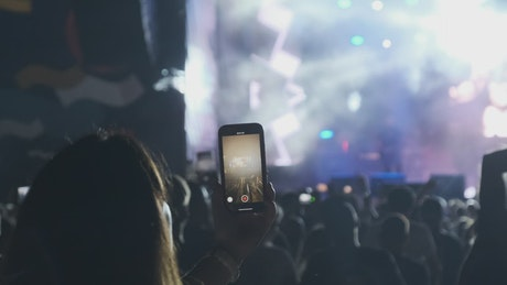 Woman recording a concert with her smartphone