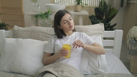 Woman relaxes in bed with juice during lockdown