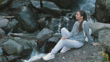 Woman relaxing by a waterfall in a forest