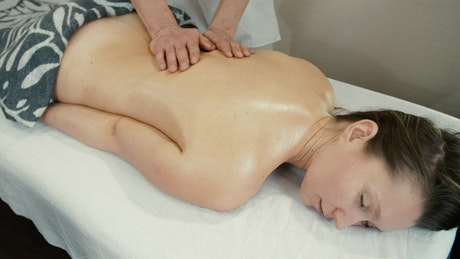 Woman relaxing while getting a back massage