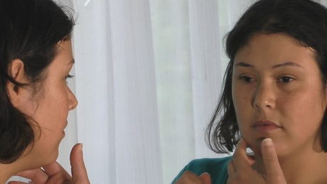 Woman removing a prosthesis eye in the mirror