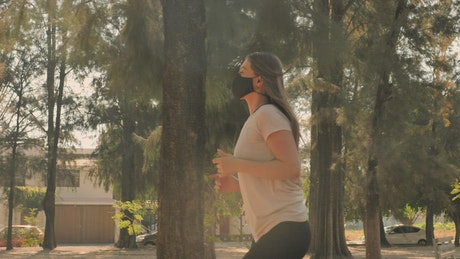 Woman running with face mask in a park