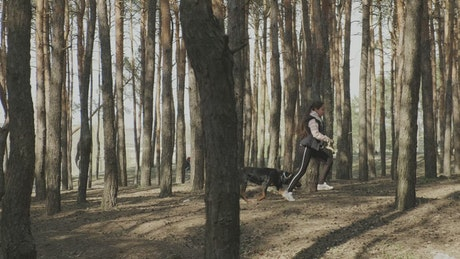 Woman running with her dog through the forest