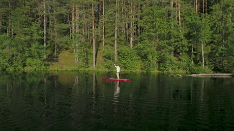 Woman sailing on a red paddleboard in the forest