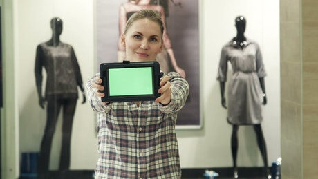 Woman showing a tablet with a green screen