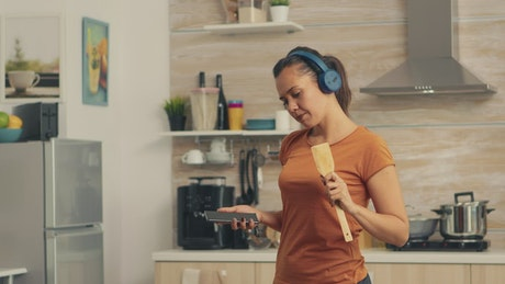 Woman singing using a spoon