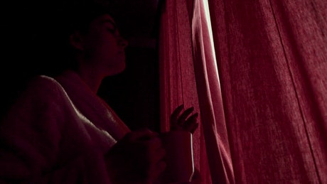 Woman sips coffee and looks through curtains in lockdown