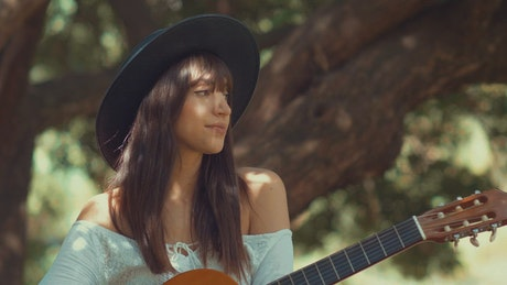 Woman sits outdoors holding a guitar