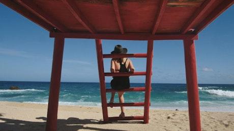 Woman sitting at lifeguard station