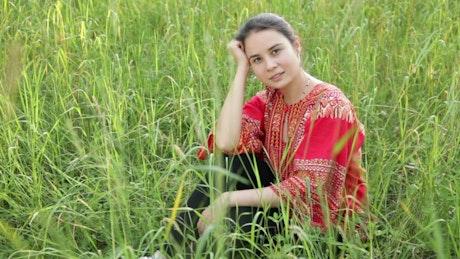 Woman sitting in a field of long grass
