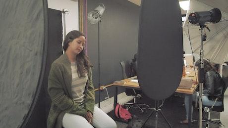 Woman sitting in a photo studio smiles