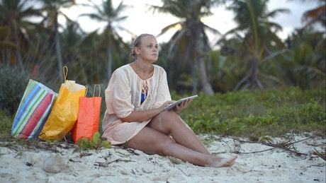 Woman sitting on the beach with her bags
