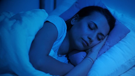 Woman sleeping in her bed in dim blue light