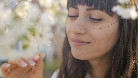 Woman smelling a daisy in a garden