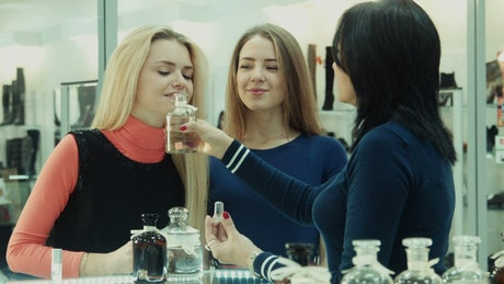 Woman smelling perfumes in the shop