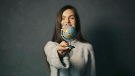 Woman spins a small world globe