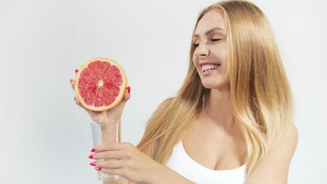 Woman squeezing a grapefruit