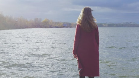 Woman standing at the edge of a cold lake