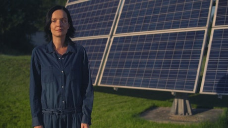 Woman standing in front of a solar panel