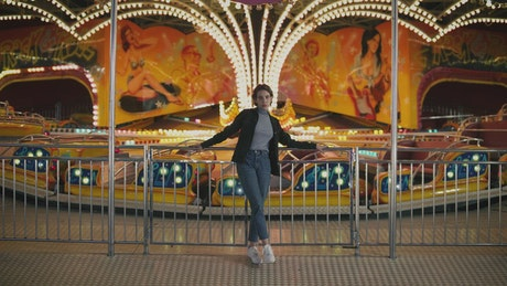 Woman standing in front of amusement park ride