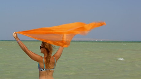 Woman standing in the wind at the beach