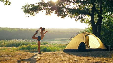 Woman stretching her body while camping in nature