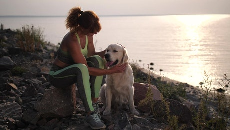 Woman stroking her dog on a shoreline at sunset