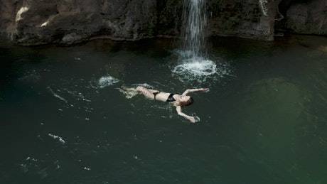 Woman swimming in a pond with a little waterfall