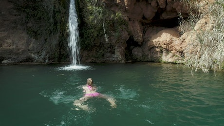 Woman swimming in a pond with a waterfall