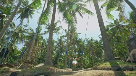 Woman swinging in the jungle on the beach