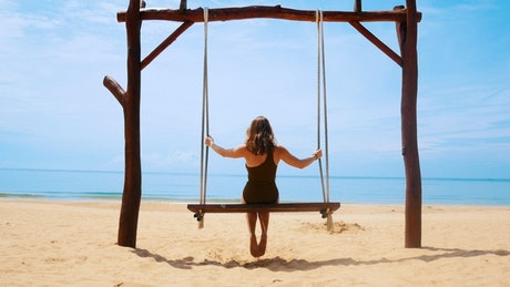 Woman swinging on a sunny beach, back view