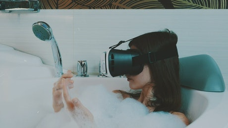 Woman taking a bath with a VR headset