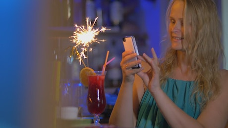 Woman taking a photo of her cocktail
