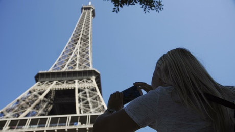 Woman taking a photo of the Eiffel tower