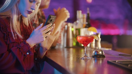 Woman taking a picture of her drinking in a bar