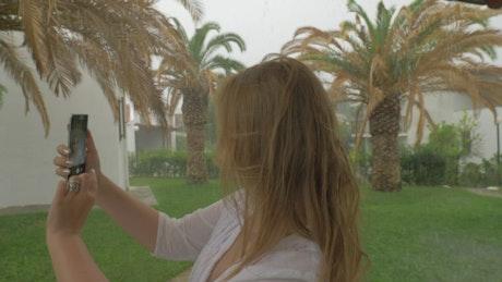 Woman taking a selfie in the rain