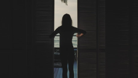 Woman taking in the ocean view from her hotel room