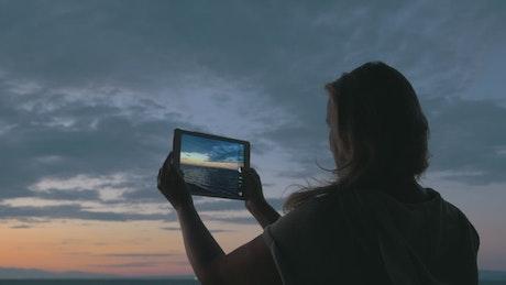 Woman taking photos at dusk