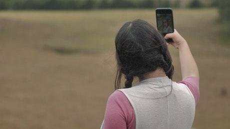 Woman taking selfies in the woods