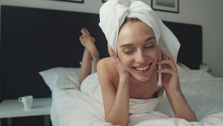 Woman talking on the phone after taking a shower