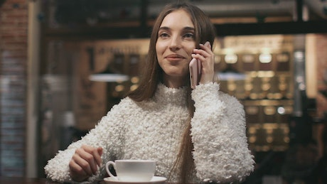 Woman talking on the phone in a coffee shop