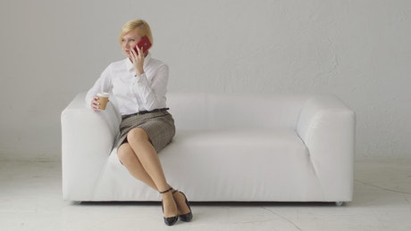 Woman talking on the phone in an armchair