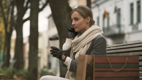 Woman talking on the phone on a public bench
