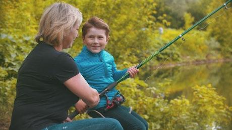 Woman teaching a boy to fish