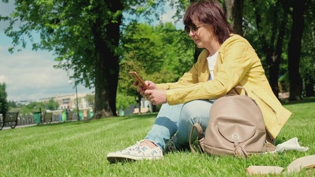 Woman texting on social media in the park