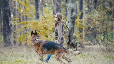 Woman throwing a stick at her dog in the woods